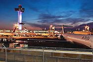 Delta Airlines aircraft parked near the control tower at New York's John F. Kennedy International Airport at dawn. WATERMARKS WILL NOT APPEAR ON PRINTS OR LICENSED IMAGES.