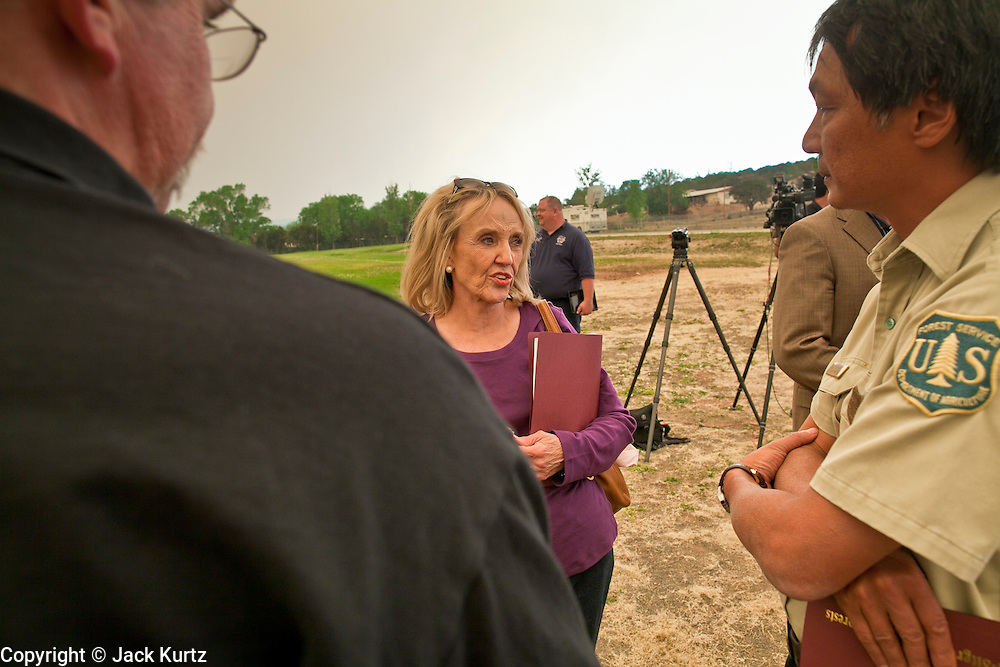 """04 JUNE 2011 - EAGAR, AZ: Gov Jan Brewer talks to members of the fire command team at  Round Valley Primary School, talks about the Wallow Fire Saturday. Smoke from the fire, more than 20 miles from Eagar, turned the sky bright orange. The fire grew to more than 140,000 acres early Saturday with zero containment. A """"Type I"""" incident command team has taken command of the fire.  PHOTO BY JACK KURTZ"""