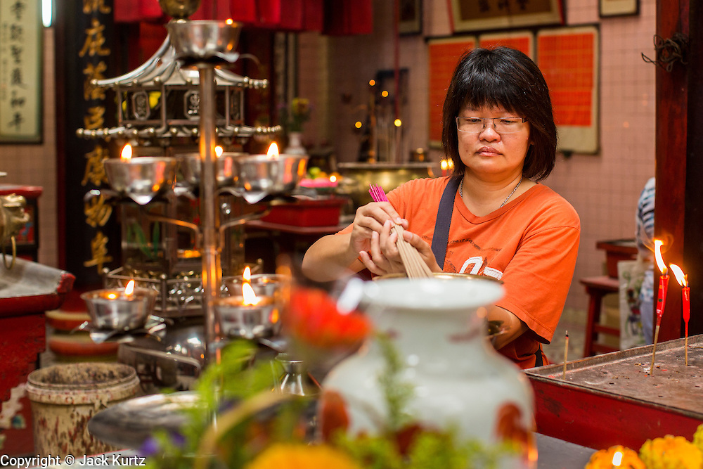 20 DECEMBER 2012 - KUALA LUMPUR, MALAYSIA:  A woman lights joss sticks (incense) in the Sin Sze Si Ya Temple, also known as the Sze Yah Temple, in Kuala Lumpur, Malaysia. The Sin Sze Si Ya Temple is the temple built by Yap Ah Loy, one of the Chinese founders of Kuala Lumpur. It is built according to Feng Shui principles and as such is not in alignment with other buildings in the neighborhood or the city grid. It is one of the oldest Chinese temples in Kuala Lumpur.  PHOTO BY JACK KURTZ