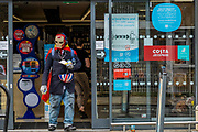 A man in an Iron man mask queues and then shops at the CO-OP in teh Munster Road - where everyone is a 'local hero' if they stay 2m from others. The 'lockdown' continues for the Coronavirus (Covid 19) outbreak in London.