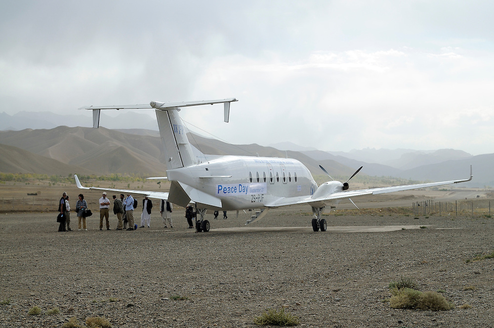 Passengers wait to board the UNHAS flight on the remote Bamiyan air field.  The airstrip is made of rocks and gravel and not entirely straight, making take off and landings more challenging in the remote mountins...