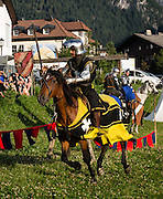 A knight in shining armor rides a horse in a medieval festival, in Selva di Val Gardena, Italy. The beautiful ski resort of Selva di Val Gardena (German: Wolkenstein in Gröden; Ladin: Sëlva Gherdëine) makes a great hiking base in the Trentino-Alto Adige/Südtirol (South Tyrol) region of Italy, in the Dolomites, part of the Southern Limestone Alps, Europe. UNESCO honored the Dolomites as a natural World Heritage Site in 2009.