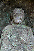 old Buddhist faceless monument inside a hillside cave