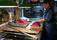 Cuts of tuna get weighted to be put on sale. Tsukiji fisk market, Tokyo, Japan 2013.