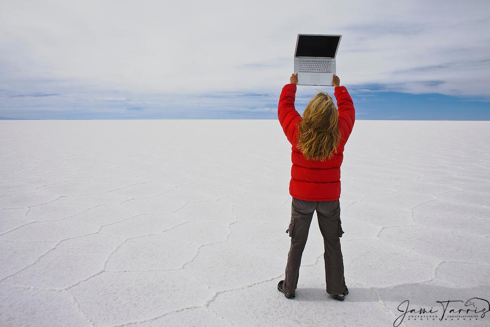 Women in red jacket standing on hexagon shaped patterns of a dry salt lake holding laptop, Salar de Uyuni, Bolivia,South America