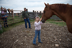 "The Nature Conservancy's Matador Ranch Operations Manager Charlie Messerly's daughter Layla plays with her horse in Eastern Montana  at the Matador ranch ""grass bank"". The ""grass bank"" is an innovative way to leverage conservation gains, in which ranchers can graze their cattle at discounted rates on Conservancy land in exchange for improving conservation practices on their own ""home"" ranches. In 2002, the <br /> Conservancy began leasing parts of the ranch to neighboring ranchers who were suffering from  severe drought, offering the Matador's grass to neighboring ranches in exchange for their  participation in conservation efforts. The grassbank has helped keep ranchers from plowing up native grassland to farm it; helped remove obstacles to pronghorn antelope migration; improved habitat for the Greater Sage-Grouse and reduced the risk of Sage-Grouse colliding with fences; preserved prairie dog towns and prevented the spread of noxious weeds. (Photo By Ami Vitale) sits on her horse in Eastern Montana  at the Matador ranch ""grass bank"". The ""grass bank"" is an innovative way to leverage conservation gains, in which ranchers can graze their cattle at discounted rates on Conservancy land in exchange for improving conservation practices on their own ""home"" ranches. In 2002, the <br /> Conservancy began leasing parts of the ranch to neighboring ranchers who were suffering from  severe drought, offering the Matador's grass to neighboring ranches in exchange for their  participation in conservation efforts. The grassbank has helped keep ranchers from plowing up native grassland to farm it; helped remove obstacles to pronghorn antelope migration; improved habitat for the Greater Sage-Grouse and reduced the risk of Sage-Grouse colliding with fences; preserved prairie dog towns and prevented the spread of noxious weeds. (Photo By Ami Vitale)"