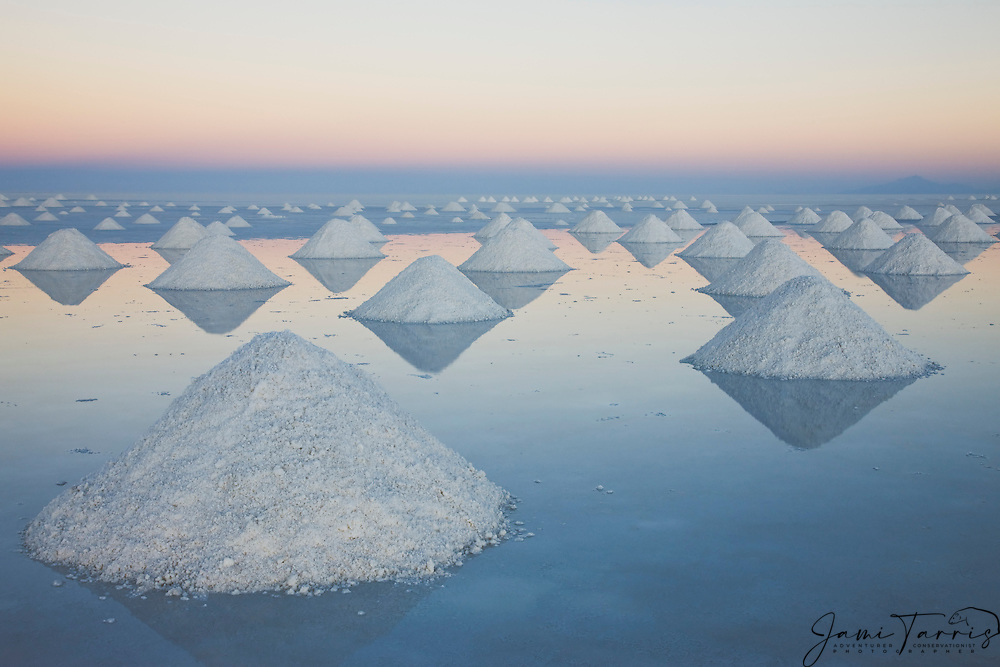 Conical mounds of salt reflected in the shallow water on the Salar de Uyuni at sunset,  Bolivia,South America