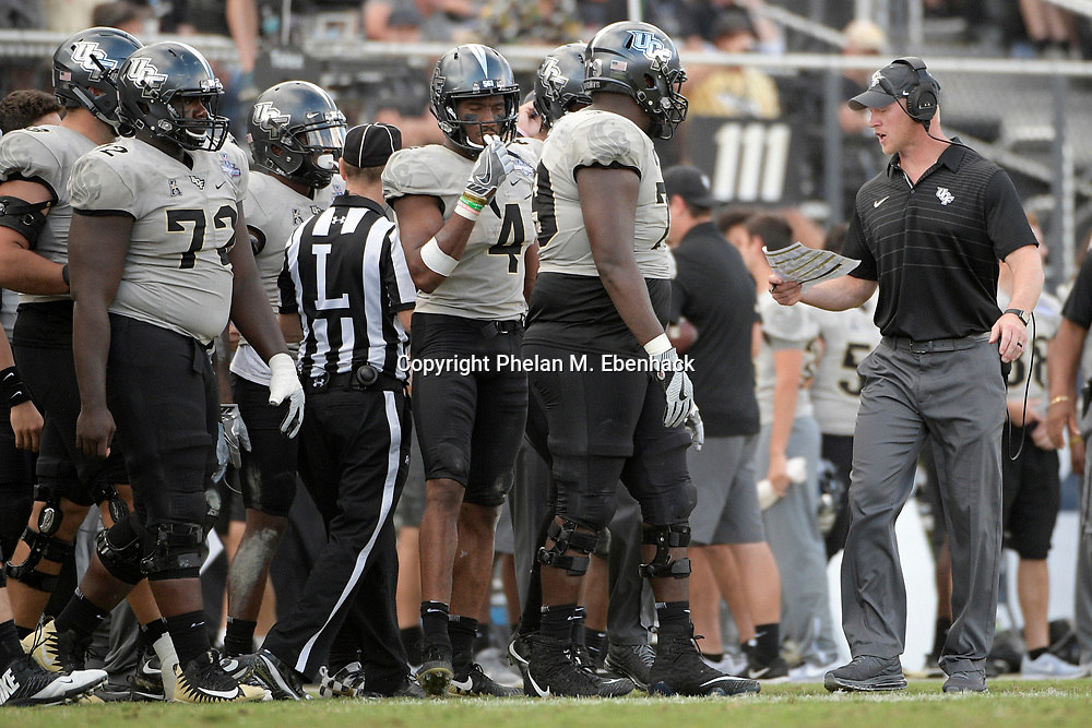 Central Florida head coach Scott Frost, right, instructs the team from the sideline during the second half of the American Athletic Conference championship NCAA college football game against Memphis Saturday, Dec. 2, 2017, in Orlando, Fla. Central Florida won 62-55. (Photo by Phelan M. Ebenhack)