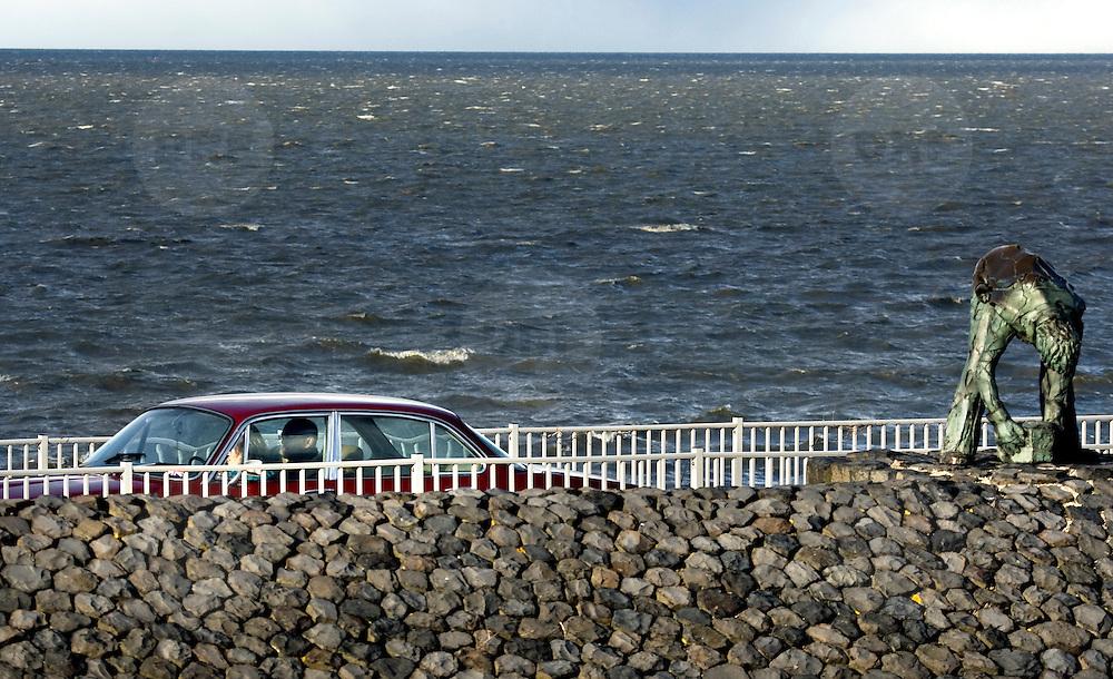 """Nederland Den Oever Zurich 22 november 2008 20081122 Foto: David Rozing ..Serie afsluitdijk. De Afsluitdijk is een belangrijke waterkering en verkeersweg in Nederland. De waterkering sluit het IJsselmeer af van de Waddenzee. Hieraan ontleent de dijk zijn naam. De verkeersweg, onderdeel van Rijksweg a7, verbindt Noord-Holland met Friesland...afsluitdijk ter hoogte van de uitkijktoren. Man bekijkt vanuit auto bronzen beeld Steenzetter.Ter gelegenheid van 50 jaar Afsluitdijk werd in 1982 het beeld de """"Steenzetter"""" van Ineke van Dijk geplaatst. Tekst: """" de strijd tegen het water blijft een strijd door en voor de mens """" standbeeld, monument, mensen, bezoekers,  deltaplan...Foto David Rozing/ Hollandse Hoogte Nederland Den Oever Zurich 22 november 2008 20081122 Foto: David Rozing ..Serie afsluitdijk. De Afsluitdijk is een belangrijke waterkering en verkeersweg in Nederland. De waterkering sluit het IJsselmeer af van de Waddenzee. Hieraan ontleent de dijk zijn naam. De verkeersweg, onderdeel van Rijksweg a7, verbindt Noord-Holland met Friesland...afsluitdijk ter hoogte van de uitkijktoren. Man bekijkt vanuit auto bronzen beeld Steenzetter.Ter gelegenheid van 50 jaar Afsluitdijk werd in 1982 het beeld de """"Steenzetter"""" van Ineke van Dijk geplaatst. Tekst: """" de strijd tegen het water blijft een strijd door en voor de mens """" standbeeld, monument, ...Foto David Rozing"""