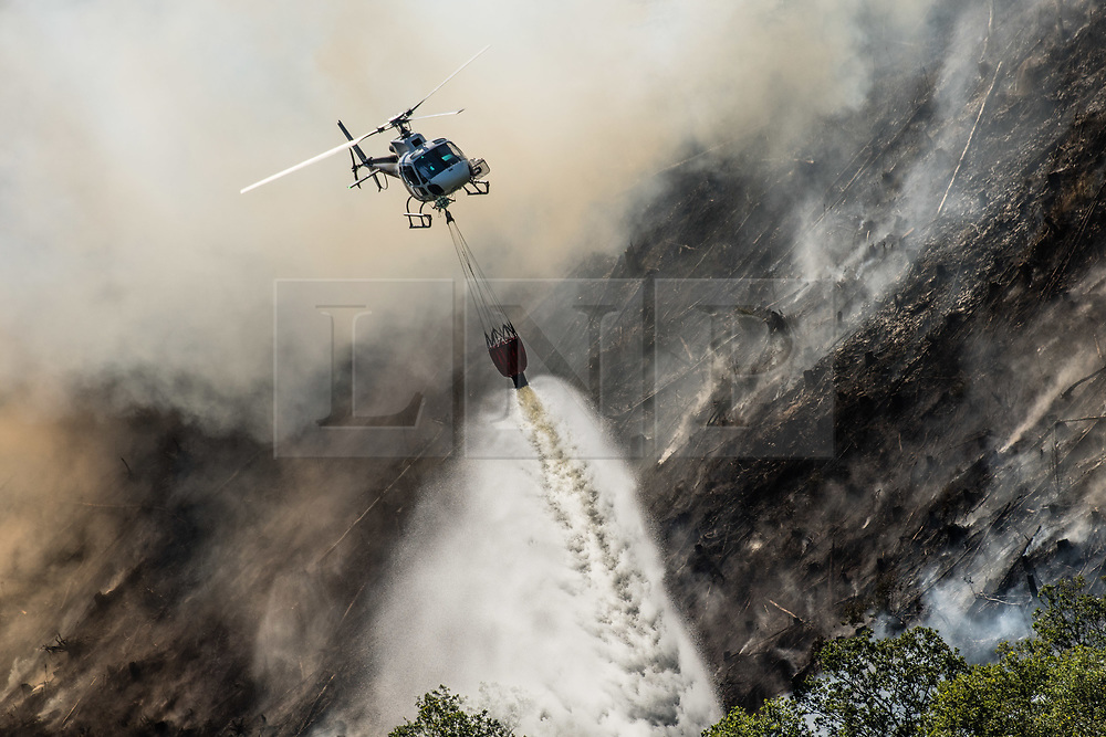 **2018 Pictures of the year by London News Pictures**<br /> © Licensed to London News Pictures. 29/06/2018. Rheidol Valley, UK. A helicopter dumps water over a forest fire that started on Tuesday  26the June  is still burning and smouldering for a fourth day along the steep hillsides of the Rheidol Valley, a few miles inland of Aberystwyth in Mid Wales. Photo credit: Keith Morris/LNP