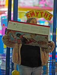 © Licensed to London News Pictures. 02/11/2020.  <br /> Crayford, UK. A masked shopper carrying a big box. Due to the second lockdown announcement by Prime Minister Boris Johnson at the weekend the number of Christmas shopping days has been halved. Shoppers on a late night panic buying spree at a Smyths toys superstore in Kent. Photo credit:Grant Falvey/LNP