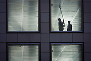 A workman wipes the ceiling of a vacant office building in the City of London. With a supervisor alongside, the worker reaches high above his head, the man uses a squeegee-type mop to clean the shiny surfaces of the ceiling and light fittings while appearing to be supervised by a second man who decides what needs cleaning next before the completion of these new corporate floors, currently unoccupied by the tenant or owner and with fixtures, fittings and furnishings still to be fitted by the property's management. Work has yet to be completed before the hundreds or thousands of employees can move in to this building in the heart of the UK capital's financial district, founded by the Romans in AD43.
