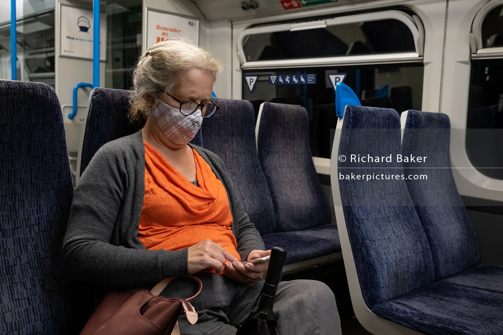A lady rail passenger on a train service through south London wears a facial covering during the Coronavirus pandemic, on 24th August 2020, in London, England.