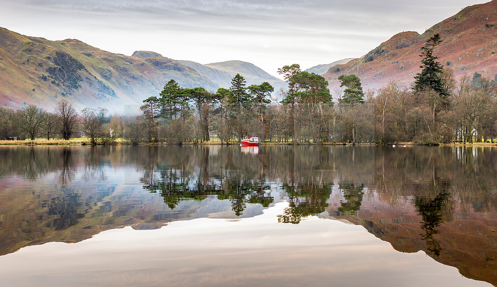 © Licensed to London News Pictures. 01/12/2020. Glenridding UK. A boat & the surrounding hills reflect into the still water of Ullswater lake in the village of Glenridding this morning in Cumbria. Photo credit: Andrew McCaren/LNP