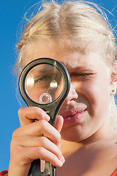 Girl (10-11) looking through magnifying glass, close-up