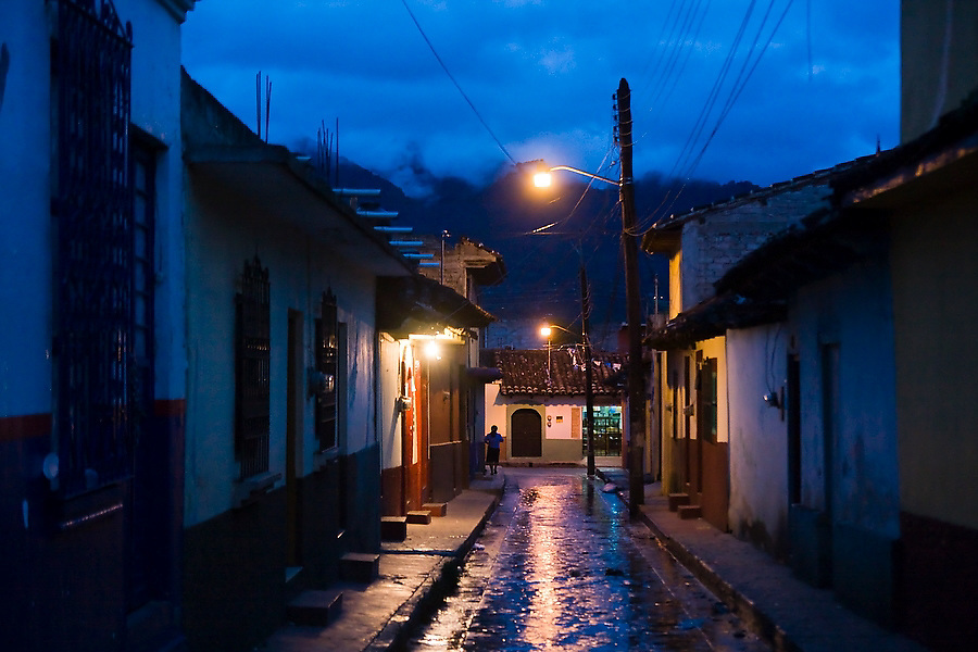 A woman walks alone down a wet and empty street at night in San Cristobal de las Casas, Chiapas, Mexico on June 24, 2008.