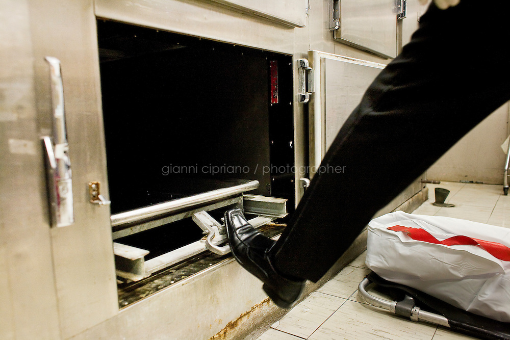 """Harlem, New York, USA - March 29. Funeral home director closes the door of the morgue drawer after he took out the corpse at the Mount Sinai Hospital on March 29, 2008 in Harlem, New York, USA. This kind of procedure is called """"removal"""". A removal consists in picking up a body at the morgue and bring it to the funeral home."""