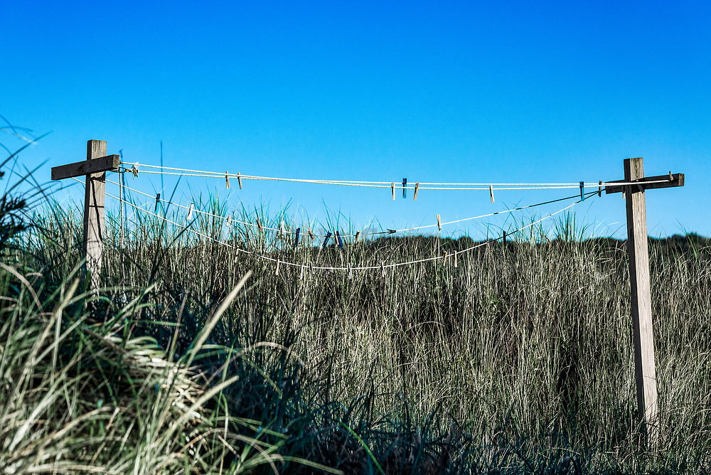 Old outdoor clothes line nestled in dune grass, Cape Cod, Massachusetts, USA