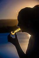 A young woman smoking marijuana in a pipe (with the Rocky Mountains in background), Littleton, Colorado USA. Colorado was the first state to legalize the sale of marijuana for recreational use in 2014.