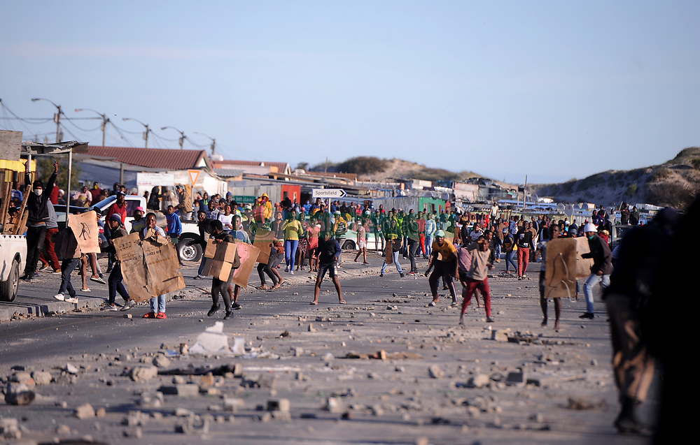 South Africa - Cape Town - 15 July 2020 -  Covid 19 Informal Settlement resident throwing stones at the police.City of Cape Town Law Enforcement officers demolishing shacks in Covid 19 Informal Settlement in Mfuleni  Photographer Ayanda Ndamane African News Agency (ANA)