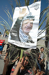 © London News Pictures. FILE PIC DATED 12/11/2004. Ramallah, West Bank.  A boy holding a poster showing the face of Yasser Arafat at the grave of Yasser Arafat after he was buried in the compound of the Muqaata in the West Bank city of Ramallah.  Scientists are due to exhume the remains of Yasser Arafat in an effort to determine whether his death in 2004 was caused by polonium-210 poisoning.   Photo credit: Grant Fleming/LNP