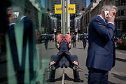 Symmetrical gentlemen talk on their phones reflected in plate glass in the City of London, the capitals financial district also known as the Square Mile, on 6th April 2017, in London, England.
