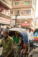 Dhaka, Bangladesh - November 1, 2017: A crowded street full of rickshaws in the historic center of Dhaka. One passenger wears earbuds.