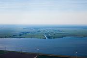 Nederland, Utrecht, Gemeente Eemnes, 06-09-2010; polders tussen Eemnes en Spakenburg gezien vanuit Flevoland. Een van de laatste open polderlandschappen in de Randstad, aan de horizon het Gooi, het riviertje de Eem mondt uit in het Eemmeer.  De polders zijn: Zuidpolder te Veld, Noordpolder te Veld, Maatpolder Bikkerspolder. .Polders between Eemnes and Spakenburg seen to Flevoland. One of the last open polder landscapes in the Randstad. The river Eem flows into the Eemmeer..luchtfoto (toeslag), aerial photo (additional fee required).foto/photo Siebe Swart