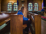 """04 APRIL 2020 - DES MOINES, IOWA: A woman prays herself in St. Anthony Catholic Church in Des Moines. The Des Moines Diocese has put all masses online but many churches are open for individuals to come in an pray by themselves. On Saturday morning, 04 April, Iowa reported 786 confirmed cases of the Novel Coronavirus (SARS-CoV-2) and COVID-19. There have been 14 deaths attributed to COVID-19 in Iowa. Restaurants, bars, movie theaters, places that draw crowds are closed until 30 April. The Governor has not ordered """"shelter in place"""" but several Mayors, including the Mayor of Des Moines, have asked residents to stay in their homes for all but the essential needs. People are being encouraged to practice """"social distancing"""" and many businesses are requiring or encouraging employees to telecommute.        PHOTO BY JACK KURTZ"""