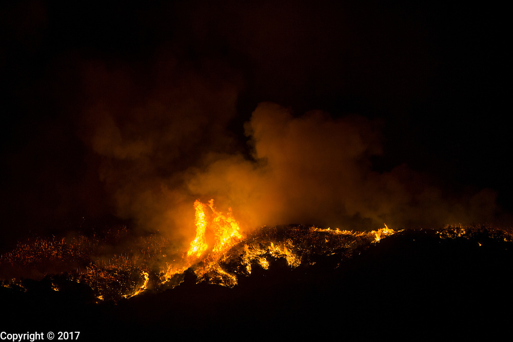 12072017 - Ojai, California USA: Fires rage in hills near the city of Ojai, California, where the Thomas fire was threatening the town. Fire crews were working to burn some of the fuel as the uncontrolled fire approached in a last stand against the fire, which was just outside town. The fire was burning toward the city from two directions. The Thomas Fire, which began Monday, has scorched over 100,000 acres. (Jeremy Hogan/Polaris)