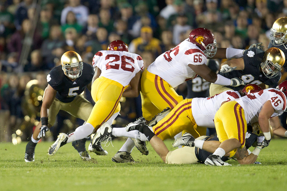 USC running back Marc Tyler (#26) rushes the ball as Notre Dame inside linebacker Manti Te'o (#5) defends during first quarter of NCAA football game between Notre Dame and USC.  The USC Trojans defeated the Notre Dame Fighting Irish 31-17 in game at Notre Dame Stadium in South Bend, Indiana.
