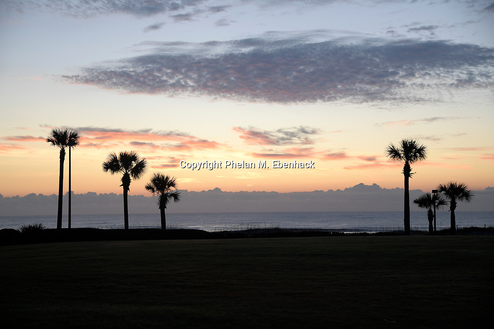Palm trees silhouetted by the sun rising over the Atlantic Ocean behind the Ritz Carlton resort Tuesday, Sept. 26, 2017, in Amelia Island, Fla. (Photo by Phelan M. Ebenhack)