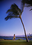 A woman stands underneath a palm tree holding snorkeling gear by the beach