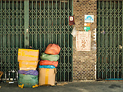 07 JUNE 2016 - BANGKOK, THAILAND: A family's belongings stacked in front of the gate to their shophouse in Verng Nakorn Kasem, also known as the Thieves' Market. Verng Nakorn Kasem was one of Bangkok's most famous shopping districts. It is located on the north edge of Bangkok's Chinatown, it grew into Bangkok's district for buying and selling musical instruments. The family that owned the land recently sold it and the new owners want to redevelop the famous area and turn it into a shopping mall. The new owners have started evicting existing lease holders and many of the shops have closed. The remaining shops expect to be evicted by the end of 2016.   Bangkok's Chinatown, considered by some to be one of the best preserved Chinatown districts in the world, is changing. Many of the old shophouses are being demolished and replaced by malls and condominium developments.        PHOTO BY JACK KURTZ