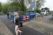 Een jonge vrouw passeert een van de vele plaatsen in Utrecht waar gewerkt wordt. Utrecht is bezig met het herinrichten van het centrum, wat gepaard gaat met de nodige overlast.