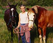 Heather Robbins with free-ranging horses belonging to Raspbery Island Lodge, Raspberry Island, Kodiak Archipelago, Alaska.
