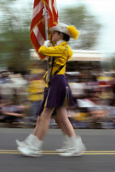 Americana Color guard of high school marching band  marches in small town holiday celebration parade. Stock photo