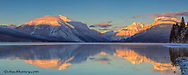 Panoramic of sunset alpenglow on mountain peaks reflecting into Lake McDonald in winter in glacier National Park, Montana, USA