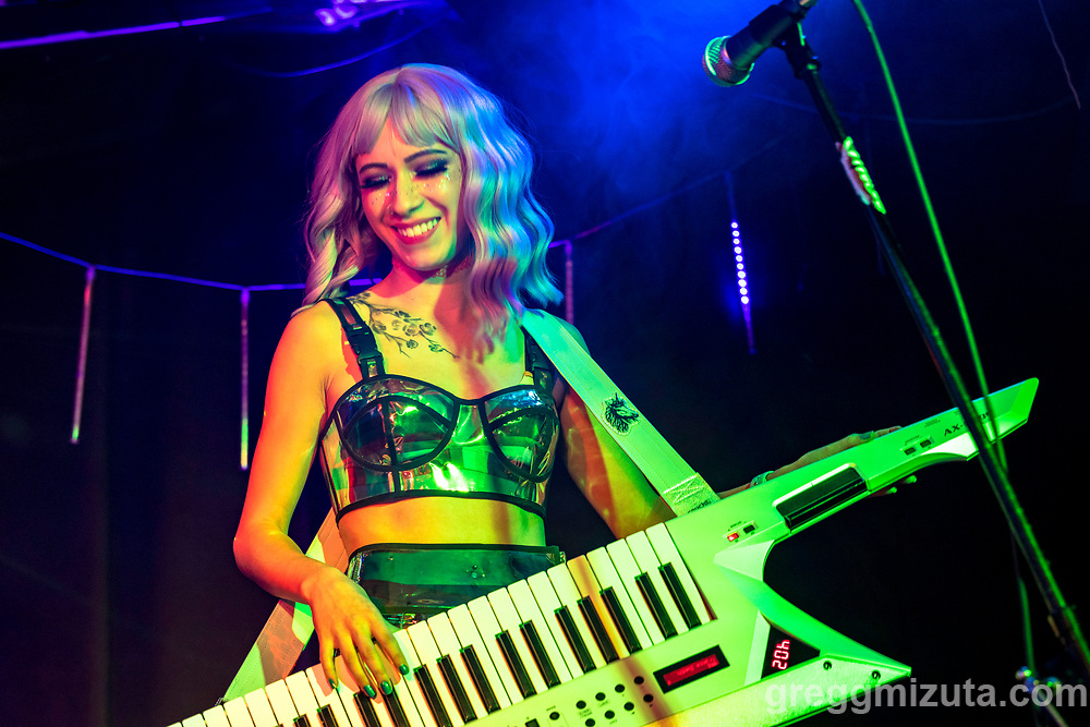 """Ari Wing. HE/LIUM SHE/LIUM performs at the Boise Hive, Boise, Idaho on August 21, 2021.<br /> <br /> HE/LIUM SHE/LIUM is an 80's inspired, synth pop, electronic, dance duo.<br /> <br /> They started when partners Ari Wing and Rocky Wing found themselves in a small apartment in Boise, ID. With no connections, working full-time, going to school, lack of practice space, and the noise limits of apartment living, they decided to go fully electronic. (No real instruments are harmed in the making of their music.)<br /> <br /> Ari plays keytar and sings. Rocky plays all the other sounds on a midi controller. What makes them unique is that, although they play loops, they actually create those loops in real time while they are playing. So that means that if they make a mistake (or reinterpretation!) it repeats for the whole song. It makes for exciting, spontaneous live shows.<br /> <br /> Their sound is infectious and will get you on your feet. Don't be surprised if you are singing along to a song you just heard! Yet at the same time their connection to each other, their music, and the audience is authentic and genuine. Their lyrics balance beautifully between the bleak reality of past rejection and the positive vibes that is their life together now. Even their sound guy at one of their shows confessed afterwards """"I usually like dark metal. I don't want to like you guys. But I can't help it -- I love HE/LIUM SHE/LIUM!"""""""
