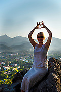 A woman makes a heart sign with her hands in the fading evening light atop Mount Phousi, Luang Prabang, Laos.