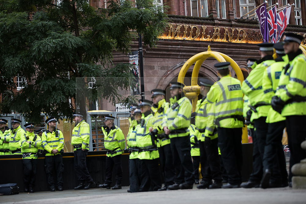 © Licensed to London News Pictures . 01/10/2017. Manchester, UK. Police ring of steel prevents protesters from approaching the Midland Hotel . Anti Tory protesters block tramtracks leading to the network having to halt services at St Peter's Square opposite the Midland Hotel . People take part in a demonstration against the Conservative Party in Manchester during the Conservative Party Conference , which is taking place at the Manchester Central Convention Centre . Photo credit: Joel Goodman/LNP