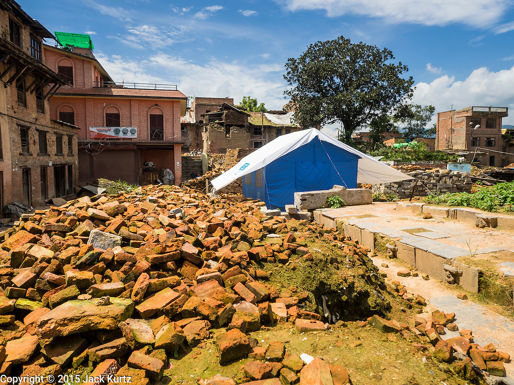 04 AUGUST 2015 - BUNGAMATI, NEPAL: Bricks stacked up around the site of the Hindu temple in Bungamati, a village about an hour from Kathmandu. The temple was destroyed in the earthquake and the plaza around the temple has been turned into an Internal Displaced Person (IDP) camp. Three months after the earthquake debris from the earthquake still clogs many of the streets in the community. The Nepal Earthquake on April 25, 2015, (also known as the Gorkha earthquake) killed more than 9,000 people and injured more than 23,000. It had a magnitude of 7.8. The epicenter was east of the district of Lamjung, and its hypocenter was at a depth of approximately 15km (9.3mi). It was the worst natural disaster to strike Nepal since the 1934 Nepal–Bihar earthquake. The earthquake triggered an avalanche on Mount Everest, killing at least 19. The earthquake also set off an avalanche in the Langtang valley, where 250 people were reported missing. Hundreds of thousands of people were made homeless with entire villages flattened across many districts of the country. Centuries-old buildings were destroyed at UNESCO World Heritage sites in the Kathmandu Valley, including some at the Kathmandu Durbar Square, the Patan Durbar Squar, the Bhaktapur Durbar Square, the Changu Narayan Temple and the Swayambhunath Stupa. Geophysicists and other experts had warned for decades that Nepal was vulnerable to a deadly earthquake, particularly because of its geology, urbanization, and architecture.    PHOTO BY JACK KURTZ