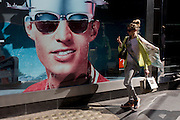 A trendy young woman passes-by a poster of a model showing stylish shades outside a sunglasses shop window selling Ray Bans on Long Acre in London's Covent Garden.