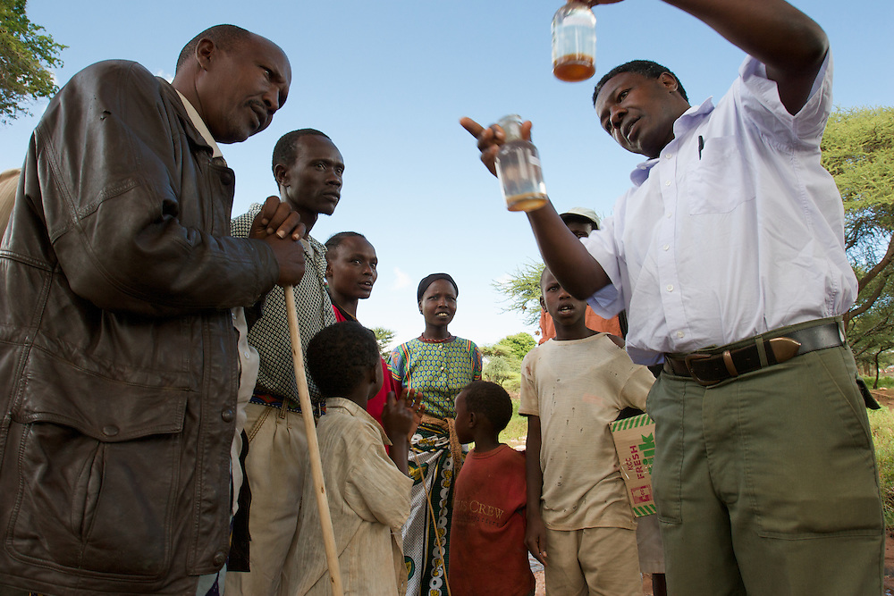 Scientist shows local Samburu villagers and farmers results of water sample testing from bore hole used to irrigate crops.