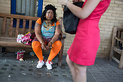 Woman in orange leggings sitting smoking a cigarette on a bench outside a hospital in London, UK. Her general demeanor was of someone who was troubled or unhappy with her situation. Another woman passes and their lives seem totally different.