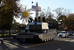 November 11, 2018 - Washington, DC, U.S - A fake tank with a giant artificial flower in its gun turret and someone holding up an American flag being driven through Washington, DC on Veterans Day.  The tank is shown on 17th Street NW near E Street being followed by a police car.  The Washington Monument can be seen in the background. (Credit Image: © Evan Golub/ZUMA Wire)
