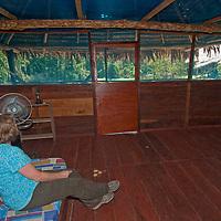 A traveler surveys her hut at the Amazon Refuge Wildlife Conservation Center in Peru's Amazon Jungle.