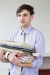 Portrait of businessman holding stack of files in office, smiling