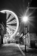 An arc of light from Sheffield's Big Wheel and a starburst of light from the street lamp make this urban scene from Norfolk Row. A nighttime cityscape in South Yorkshire, England, UK.