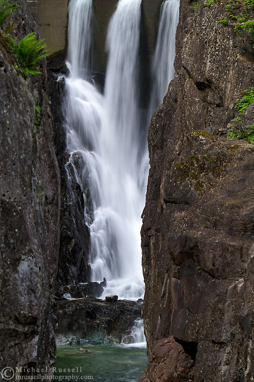 Water from Capilano Lake flows into Ring Bolt Pool under Cleveland Dam at Capilano River Regional Park in North Vancouver, British Columbia, Canada.  Photographed from the viewing area at the end of Second Canyon Trail.